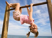 Little girl hanging upside down from high beam