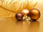 Golden christmas decoration from baubles and feather