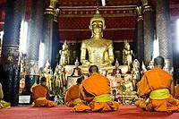 Monks praying in temple or wat Luang Prabang Laos