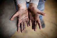 Hand of a ten years old boy dirty with black paint