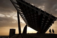 Two people walking under a giant solar panel in Barcelona
