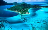 Aerial of the green water and clear blue colors of the islands of Bora Bora in Tahiti in French Polynesia