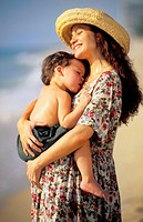 Beautiful pregnant hispanic mother with her young son with love together at beach with waves