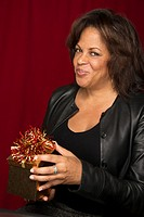 A beautiful middle-aged black woman opens a gift box with a wry grin