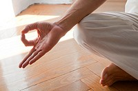 Close view of man's hand practicing yoga, sitting in the lotus position.