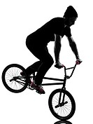 one caucasian man exercising bmx acrobatic figure in silhouette studio isolated on white background.