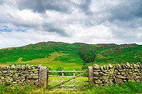 A dry stone wall and gate in the Lake District with Gowbarrow Fell in the distance, Cumbria, England.