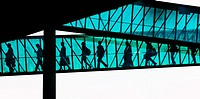 Passengers disembark from an aeroplane through the enclosed passage ramp. They are silhouetted against the sunlight