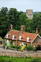 Red brick cottages with dormer windows and gardens and Church of St. Lawrence in village of Castle Rising, Norfolk, England.