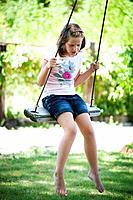 young girl swinging in beautiful greenery