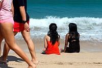 Two girls sitting on the beach, Java Sea, Bali, Indonesia, Southeast Asia.