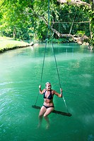 Woman on a swing in the Blue Lagoon in Vang Vieng, Laos.
