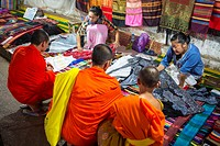 Monks buying fabric at the night market in Luang Prabang, Laos.