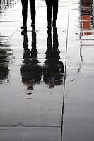 two men walking on wooden floor boards in city town