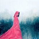 Woman wearing red cloak walking outdoors.