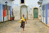 Local brazilian woman walking through the historic center; Paraty, Espirito Santo, Brazil. The beautiful colonial town of Paraty has been a UNESCO Wor...