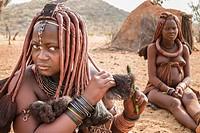 Himba woman combing her hair, village near Epupa falls, Kunene, Namibia, Africa.