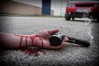 Man with gun in hand bloodstained lies dead in the asphalt murder victim.