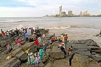 indian people enjoy fresh breeze from arabian sea on a rocky area outside the haji ali´s mosque and tomb in worli district. mumbay. maharashtra. india...