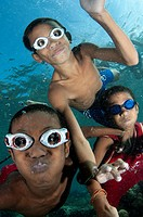 Trio of boys with goggles playing in the water at Pura Island near Alor in eastern Indonesia.