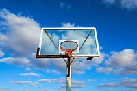 Basketball hoop and backboard with clouds overhead. San Diego, California, United States.