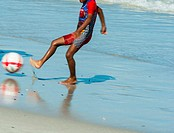 A young African lad dressed in a sun-protective bathing suit, kicks a ball on the beach at low tide. Cape Town South Africa