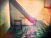 A stool sits on a grungy floor in front of a staircase in a an abandoned house. Ontario, Canada.