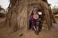 Mursi woman with lip plate in the Lower Omo Valley of Ethiopia. The Mursi girls have a fold cut in their lower lip as they enter womanhood, where a pu...