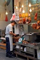 Hong Kong, China, Asia. Hong Kong Kowloon. Roadside butcher with large knife at work.