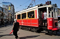 The old tram in the confluence of Istiklal Cadessi and Taksim Square and Turkcell cellular phone operator publicity placard . Istanbul. Turkey.