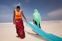 Young muslim girls in colorful dress with fishnet on Jambiani beach, Zanzibar Island, Tanzania, East Africa.