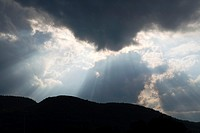 Sun rays stream from a cloud above the Adirondack Mountains near Ticonderoga in upstate NY, USA, North America