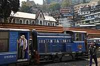 "Tourists and locals board and depart The Darjeeling Himalayan Railway station. Known as the """"Toy Train"""", it is a 2 ft (610 mm) narrow gauge railway ..."