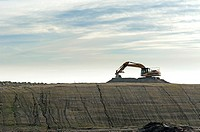 Canada, BC, Delta. Excavator silhouetted against sky on construction site preload, River Road.