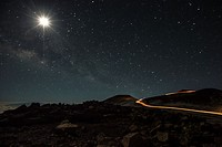 The Milky Way and Moon from the summit of Haleakala, Hawaii. Car tail lights and headlights snake further up the summit to the observatory.