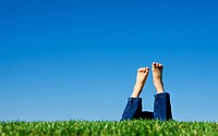 A conceptual image of the feet of a child in the grass shown on a bright summer day against a blue sky.