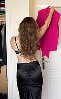 Young woman trying on clothes before going out.