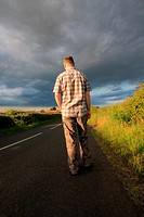 A man walking on the rural road in the golden sunlight.