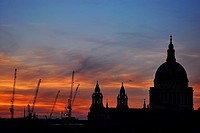St. Paul´s Cathedral in London, England, and cranes from the many building sites near it, seen against a spectacular sunset.