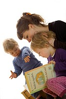 family reading childrens book, mom with son and daughter, white background.