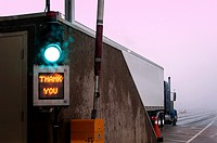 A truck in foggy conditions at an automated toll booth, Nova Scotia. Thank You and green light indicate that the correct toll has been received.