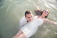 Young man dressed up in a party suit, holding afloat in shalow sea a young woman in a white party dress.