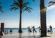 View of a persons practising Tai Chi on Albir beach, Alicante province, Spain.
