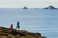Two female hikers look out to sea, Crozon Peninsula, Finistere, Brittany, France.