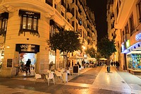 Carrer del Convent de Santa Clara pedestrian street with cafe tables at night.