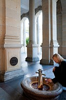 Blond woman fills a typical ceramic mug with thermal mineral waters at one of five springs at Mill Colonnade, Karlovy Vary (Karlsbad), Czech Republic.