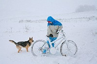 girl with her dog picking up bicycle in a snowy day. Spain