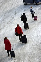 people pulling wheeled luggage walk across ice at kirkenes harbour finnmark norway europe.