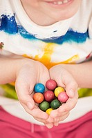 Little girl (5 years) holding colorful toy marbles in her hands. A moment of childhood fun and leisure games.