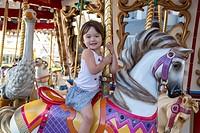 Happy girl riding the merry go round.